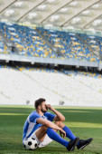 Photo sad professional soccer player in blue and white uniform sitting with ball on football pitch at stadium