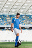 professional soccer player in blue and white uniform with ball on football pitch at stadium