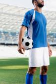 Fotografie oříznutý pohled profesionálního fotbalisty v modré a bílé uniformě s míčem na fotbalovém hřišti na stadionu