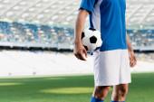 Fotografie Ausgeschnittene Ansicht eines Fußballprofis in blau-weißer Uniform mit Ball auf dem Fußballplatz im Stadion