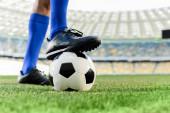 Fotografie nohy profesionálního fotbalisty v modrých ponožkách a fotbalové boty na míči na stadionu
