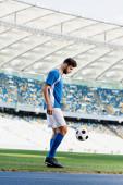 oldalnézetben professzionális focista kék-fehér egyenruhában labdával a stadionban