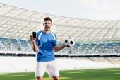 profi focista kék-fehér egyenruhában, golyóálló okostelefonnal, üres képernyővel és kiabálással a stadionban