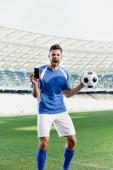 Fényképek profi focista kék-fehér egyenruhában, golyóálló okostelefonnal, üres képernyővel és kiabálással a stadionban