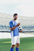 smiling professional soccer player in blue and white uniform with ball using smartphone at stadium