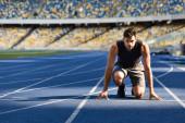pohledný běžec na startovním místě na běžecké dráze na stadionu