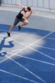 hezký běžec cvičení na běžecké dráze na stadionu