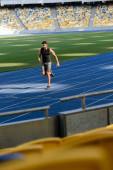 szelektív fókusz gyors jóképű futó gyakorló futópálya stadionban