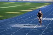 rychlý hezký běžec cvičení na běžecké dráze na stadionu