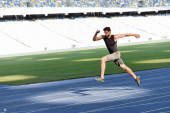 Photo fast handsome runner exercising on running track at stadium