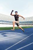 Fotografie hezký běžec cvičení na běžecké dráze na stadionu
