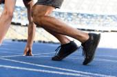 Ausgeschnittene Sicht auf Läufer in Startposition auf Laufstrecke am Stadion