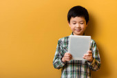cute smiling asian boy using digital tablet on yellow