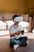 KYIV, UKRAINE - 22. 4. 2020: dětská videohra s joystickem a sluchátky virtuální reality na vlastní izolaci