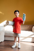athletic asian boy holding sports bottle and fitness mat at home during self isolation