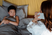 Photo diseased asian boy lying in bed while mother calling to doctor on quarantine