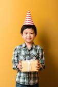 roztomilý asijské chlapec v strana kužel držení dárek k narozeninám na žluté