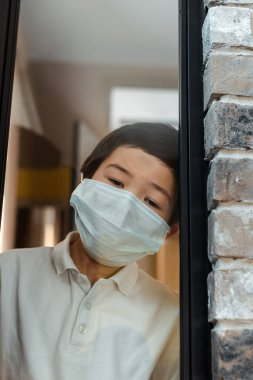 Upset asian boy in medical mask looking through window on quarantine stock vector