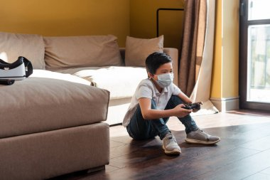 KYIV, UKRAINE - 22 Nisan 2020: Medikal maskeli Asyalı çocuk kendini izolasyon üzerine joystick ile video oyunu oynuyor