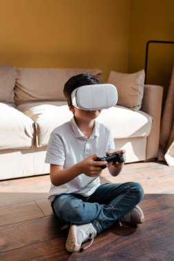 KYIV, UKRAINE - APRIL 22, 2020: child playing video game with joystick and virtual reality headset on self isolation stock vector