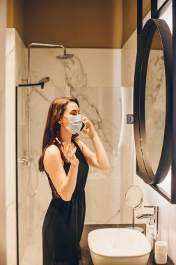 woman in black dress and medical mask holding cosmetic brush and talking on smartphone in bathroom