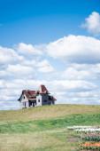 Fotografie dům na kopci v blízkosti barevné tulipány pole a modré nebe s mraky