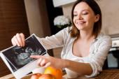 Selektiver Fokus einer glücklichen Schwangeren, die mit dem Finger auf Ultraschallfotos in der Nähe von Früchten zeigt