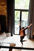 selektiver Fokus der fröhlichen und schwangeren Frau in drahtlosen Kopfhörern, die im Wohnzimmer tanzt und Musik hört