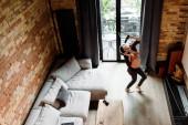 KIEW, UKRAINE - 30. APRIL 2020: fröhliche und schwangere Frau mit drahtlosen Kopfhörern tanzt und hält Fernbedienung im Wohnzimmer