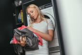 Selektiver Fokus der müden Hausfrau, die Wäsche in der Nähe der Waschmaschine hält