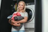 szelektív fókusz mosolygós háziasszony nézi a kamerát, miközben tartja mosoda közelében mosógép