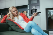 Photo serious woman sitting on sofa and holding tv remote controller