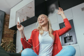 nízký úhel pohledu šťastné ženy ve sluchátkách zpěv se zavřenýma očima při držení smartphone