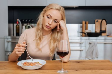Upset woman holding fork near plate with thai noodles and glass of red wine stock vector