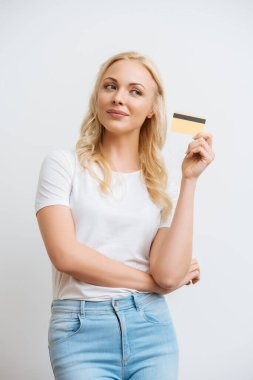 Smiling, dreamy woman showing credit card while looking away isolated on white stock vector