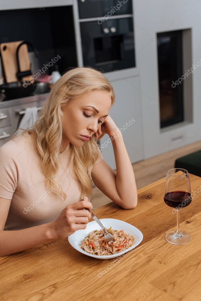 Sad woman holding fork near plate with thai noodles and glass of red wine stock vector