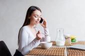 fröhliches Mädchen spricht auf Smartphone und hält Löffel mit leckeren Cornflakes in der Hand