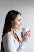 side view of cheerful woman holding cup of tea and smiling at home
