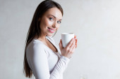 cheerful girl holding cup of tea and smiling at home