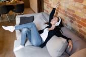 fröhliches Mädchen mit drahtlosen Kopfhörern, das im Wohnzimmer Musik hört
