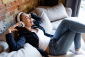 veselá dívka dotýká bezdrátových sluchátek při poslechu hudby