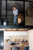mladá žena mluví na smartphone, zatímco stojí ve druhém patře v mezonetovém bytě