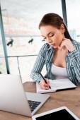 Selektiver Fokus der schönen Frau, die in einem Notizbuch in der Nähe von Laptop und digitalem Tablet mit leerem Bildschirm schreibt, Online-Studienkonzept