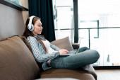 boční pohled na atraktivní volné noze v bezdrátových sluchátkách pomocí notebooku v obývacím pokoji
