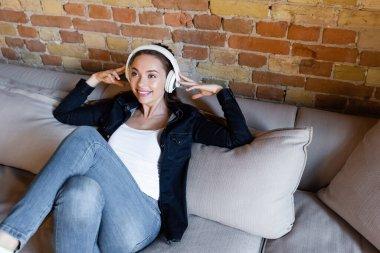 Happy girl touching wireless headphones while listening music stock vector