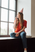 atraktivní dívka ve straně čepice sedí na parapetu a mluví na smartphone při pohledu na okno