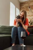 szelektív fókusz boldog fiatal nő gazdaság aranyos macska közel üveg vörösbor