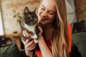 Photo happy young woman looking at cute cat at home