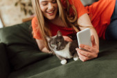 selective focus of smiling woman taking selfie with cat