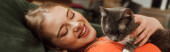 panoramic concept of cheerful woman looking at cute cat